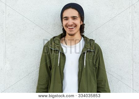 Horizontal Outdoor Portrait Of Cheerful Attractive Youngster, Smiling, Being In Good Mood, Standing