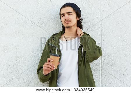 Photo Of Upset Disappointed Youngster Looking Aside, Touching His Neck With Hand, Feeling Pain, Bein
