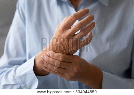 Senior Lady Massaging Hand Suffering From Rheumatoid Arthritis Concept, Closeup
