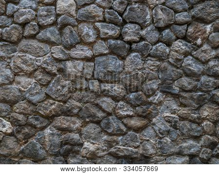 Stone Wall - Building Feature. Background Image Of Weathered Stained Old Stone Wall Of Rough Stones