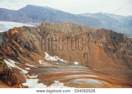 Atmospheric Alpine Landscape With Beautiful Glacial Tongue Covered With Stones And Rocky Mountain Wi