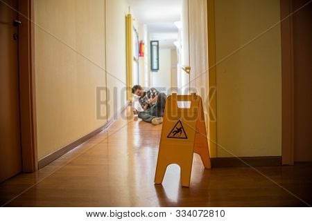 Man Slips On Wet Floor. Wet Floor Danger Sign In The Foreground. Concept Of Danger Slipping