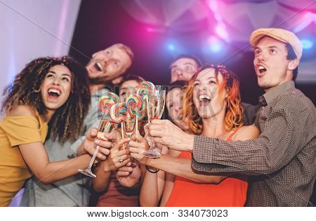 Happy Friends Having Fun Toasting With Champagne And Eating Lollipops In Disco Club - Group Young Pe
