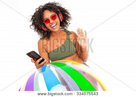 Pretty African Female In Swimsuit Stands With Big Colourful Rubber Ball, Listen To Music With Earpho