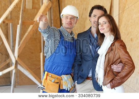 Worker in workwear shows new house from inside to a couple poster