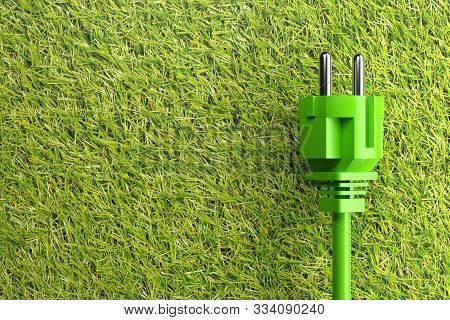 Green power cord with plug on grass background with copy space - eco or green power consumption concept, 3D illustration poster
