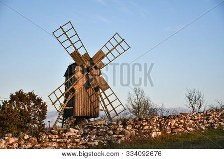 Old Wooden Windmill By A Traditional Dry Stone Wall At The Island Oland In Sweden