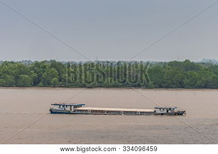 Long Tau River, Vietnam - March 12, 2019: Long Hull-closed River Barge Sails On Brown Water And Lies