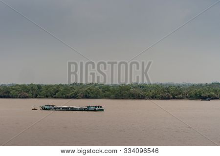Long Tau River, Vietnam - March 12, 2019: Long Segmented Hull River Barge Sails On Brown Water And L