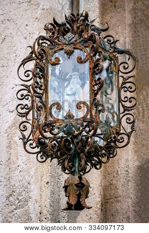 Beautiful Detailed Shot Of An Ancient Old Rusty Iron Hanging Lamp With Fragile Swirls And Electric B