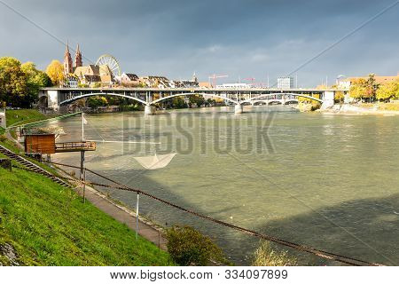 Rhine River And Old Fishing Hut In Basel Switzerland And With Old City Center Of Basel With Munster