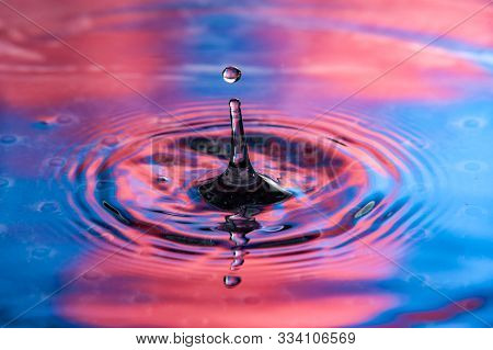 Single Water Drop At Top Of Splash. Vibrant Red And Blue Colors, High Speed Water Drop Photography