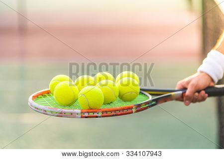 Close Up Of Tennis Player Hands Holding Tennis Racket Full Of Balls. Guy Playing Tennis One To One .
