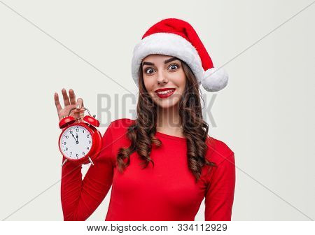 Astonished Young Female In Santa Hat Showing Alarm Clock And Looking At Camera During New Year Count