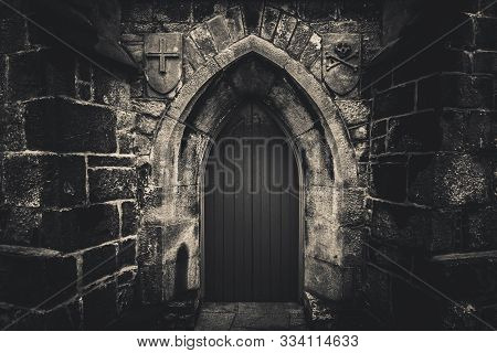 Scary Pointy Wooden Door In An Old And Wet Stone Wall Building With Cross, Skull And Bones At Both S