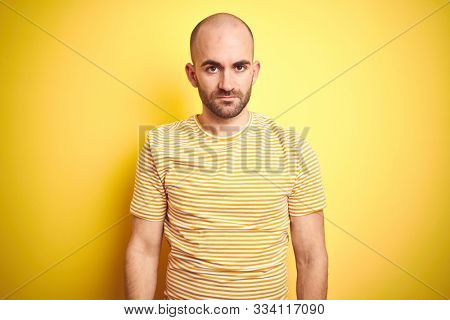 Young bald man with beard wearing casual striped t-shirt over yellow isolated background Relaxed with serious expression on face. Simple and natural looking at the camera.