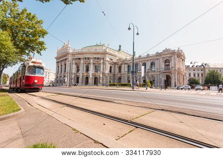 Burgtheater In Vienna With A Bright Red Tram Passing By In The Daytime In Sunny Weather, Austria