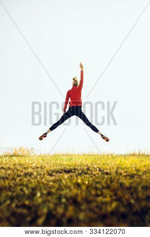 Young Athletic Girl In A Jump With Hand Raised Up. The Concept Of Sport, Healthy Lifestyle And Succe