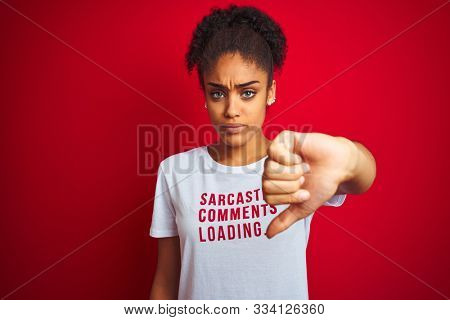 Afro american woman wearing funny t-shirt with irony comments over isolated red background with angry face, negative sign showing dislike with thumbs down, rejection concept
