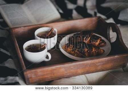 Two Cups Of Tea With Cinnamon Sticks And Anise Stars And Two Croissants On A Plate In A Cozy Room