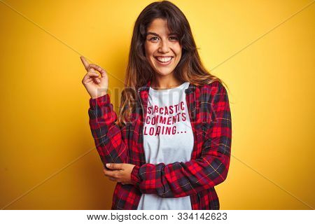 Beautiful woman wearing funny t-shirt with irony comments over isolated yellow background very happy pointing with hand and finger to the side