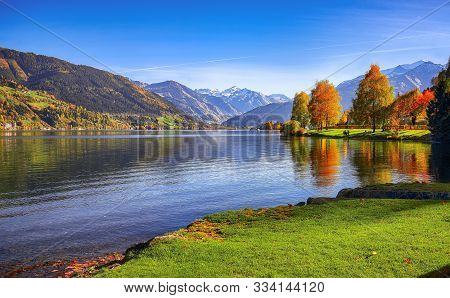 Spectacular Autumn View Of Lake And Trees In City Park Of Sell Am See. Fantastic Sunny Day Over Lake