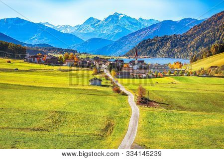 Magnificent Autumn View Of St.valentin Village And Haidersee (lago Della Muta) Lake With Ortler Peak