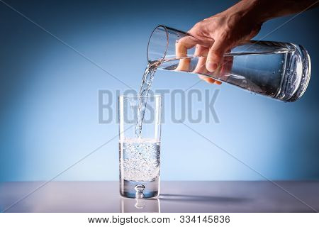 Pouring Drinking Water From A Pitcher Into A Glass. Clean Drinkable Water Concept