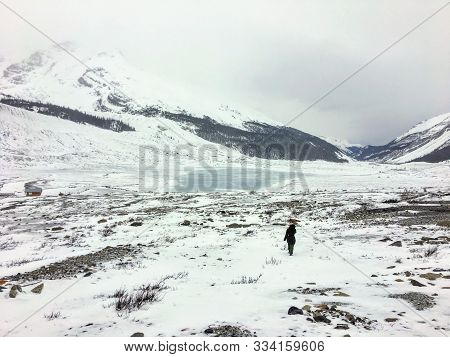 A Distant Faraway View Of A Female Hiker Alone Walking Through The Vast Winter Landscape Towards The