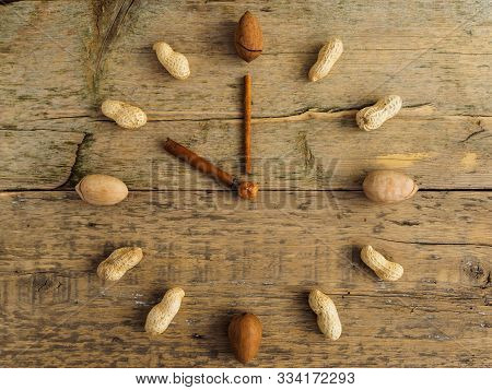 Clock Made Of Different Nuts And Cinnamon On Wooden Background. The Clock Strikes Ten O'clock. Hours