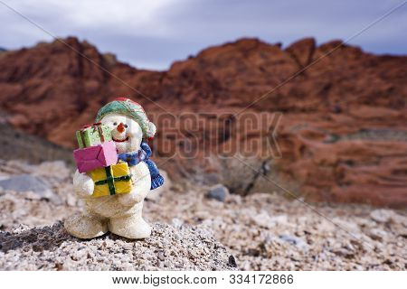 Snowman Figurine In Dry Desert Setting With Sandstone Mountains In The Background.