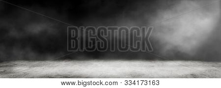 Empty Space Of Studio Dark Room With White Fog And Concrete Floor For Interior Decoration.