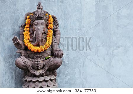 Ganesha Sitting In Meditating Yoga Pose In Front Of Hindu Temple. Decorated For Religious Festival B