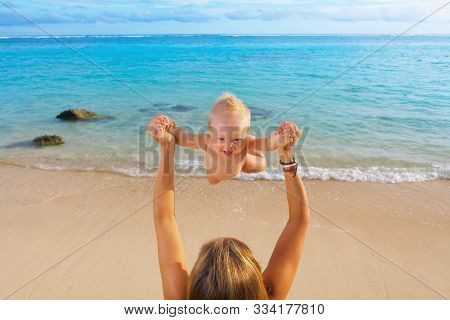 Young Happy Mother Tossing Up To Mid Air Joyful Baby Boy On White Sand Sea Beach. Outdoors Healthy C