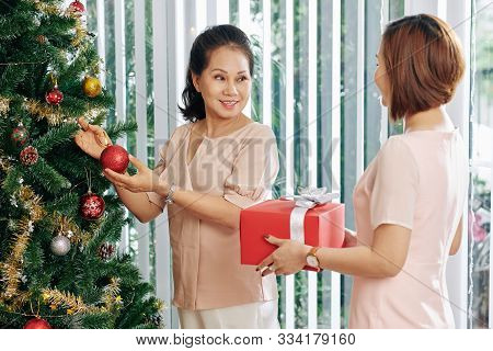 Woman Giving Present To Her Smiling Senior Mother Decorating Chirstmas Tree