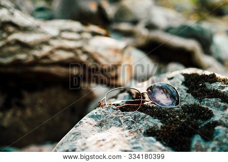 Broken Sunglasses On Stone With Moss In Sunlight. Lost Thing On Mossy Boulder In Sunny Day. Glare On