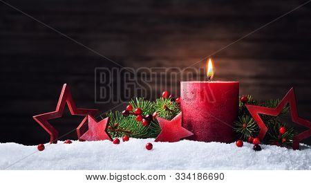 Advent Candle, Fir Tree Branches And Holiday Star Decorations In Snow Against Wooden Background. Chr