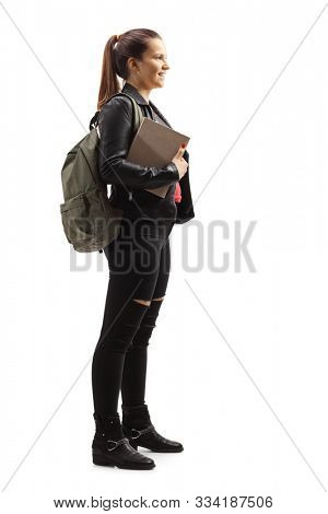 Full length profile shot of a female student holding a book and smiling isolated on white background