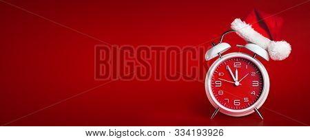 Red clock with Christmas Santa hat. Time for Christmas shopping concept.