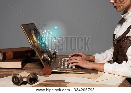 Cropped View Of Woman Typing On Steampunk Laptop With Glowing Digital Illustration At Table Isolated