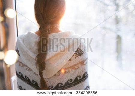 Thoughtful young brunette woman wearing nordic print poncho looking through the window, blurry winter woods snow landscape outside