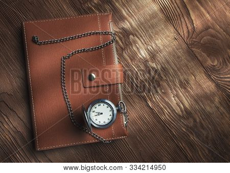 Close Up Leather Diary And Retro Watch On A  Wooden Brown Background Sun Light