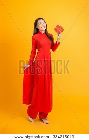 Portrait Of An Asian Girl In A Traditional Vietnamese Dress, Ao Dai, A Good Smile, Holding Gift Box