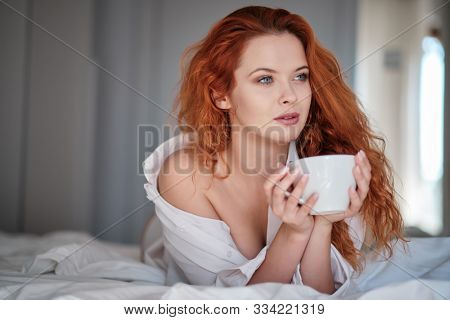 Attractive redhaired woman with a cup of coffee on the bed