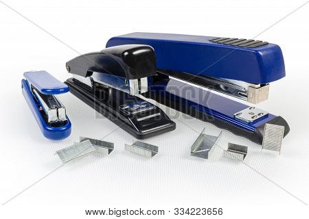 Paper Manual Hand-held Staplers Different Sizes And Expendable Metal Staples To Them On A Light Surf