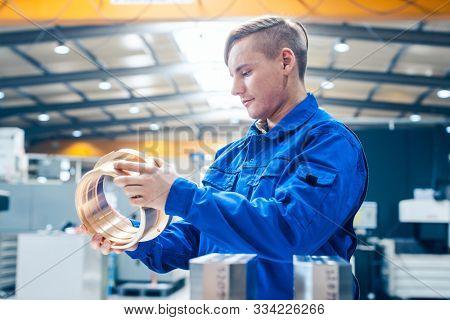 Apprentice in metalworking looking at workpiece being satisfied