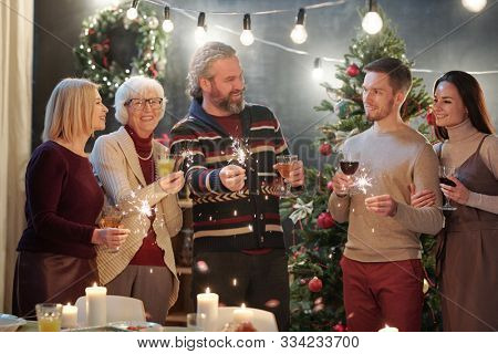 Cheerful adults with sparkling bengal lights chatting at Christmas party at home with decorated firtree on background