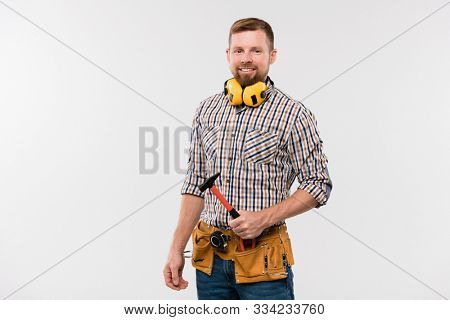 Bearded smiling technician with protective earphones, hammer and tool belt standing in front of camera in isolation