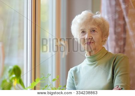 Portrait Of Beautiful Smiling Senior Woman With Curly White Hair. Elderly Lady Is Standing By Window