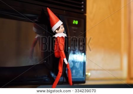 Philadelphia, Usa - 28 October 2018:funny Christmas Toy Elf On Shelf Near Microwave. American Christ